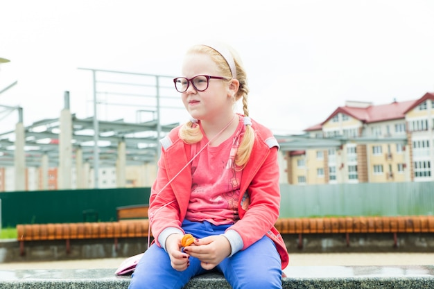 Portrait of a serious girl wearing glasses on a city street