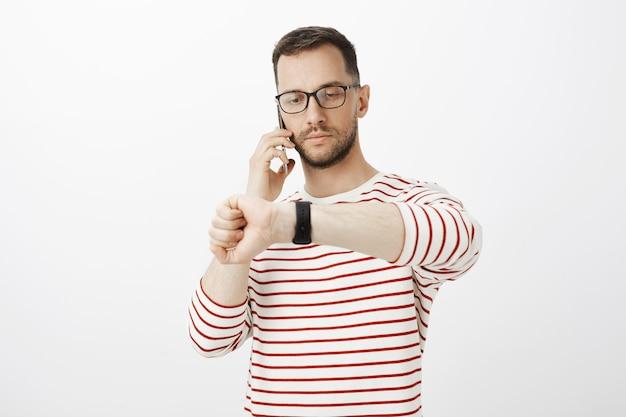 Ritratto di uomo d'affari serio di bell'aspetto in bicchieri, parlando su smartphone e guardando l'orologio, trattare con il partner commerciale e decidere il momento della riunione