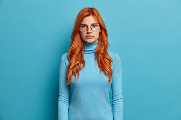 Portrait of serious good looking ginger woman looks directly stands with hands down and has self confident expression dressed in blue turtleneck and spectacles.