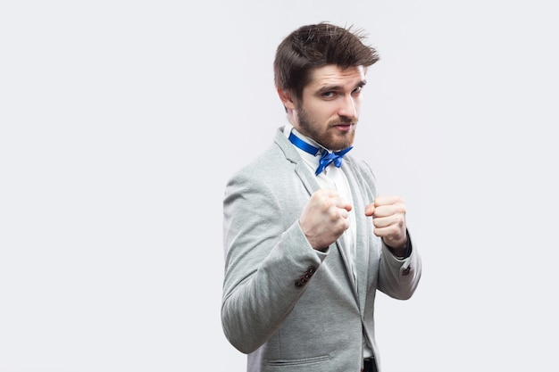 Portrait of serious handsome bearded man in casual grey suit and blue bow tie standing and looking at camera with boxing fists and ready to attack. studio shot, isolated on light grey background.