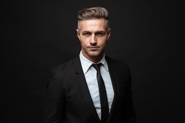 Portrait of serious handsome businessman dressed in formal suit posing and looking at camera isolated over black wall