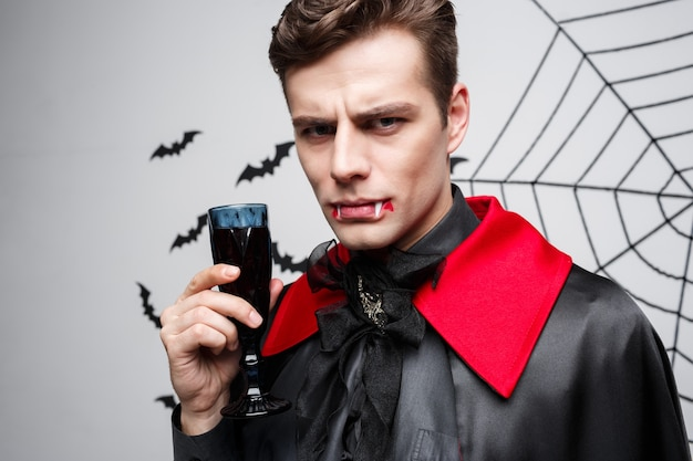Portrait of serious handsome caucasian vampire enjoy drinking bloody red wine.