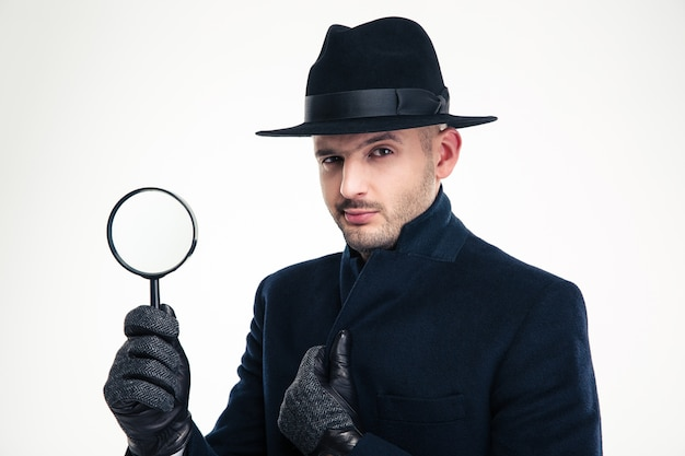 Portrait of serious handsome detective in black coat, hat and gloves holding magnifying glass over white wall