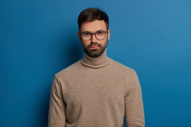 Portrait of serious handsome male has dark hair, thick bristle, looks straightly at camera, wears optical glasses and turtleneck jumper, isolated over blue background