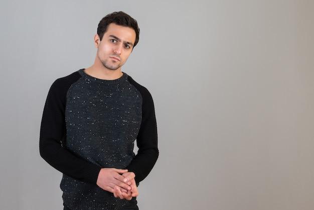 Ritratto di un bell'uomo serio in maglione nero in posa sul muro grigio
