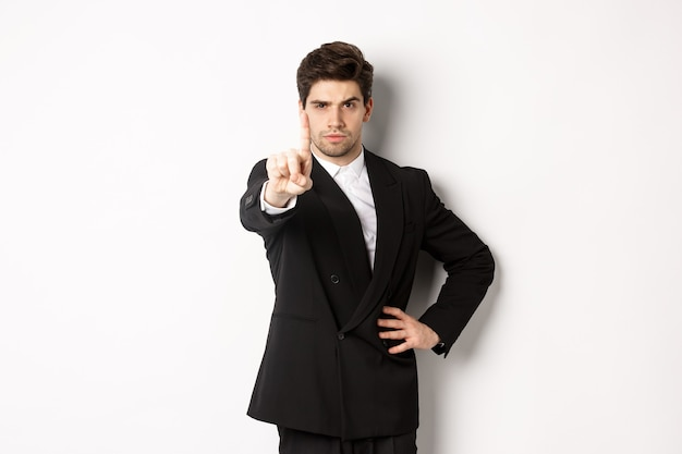 Portrait of serious handsome man in business suit, showing one finger to prohibit or decline something, telling to stop, disagree with you, standing over white background.