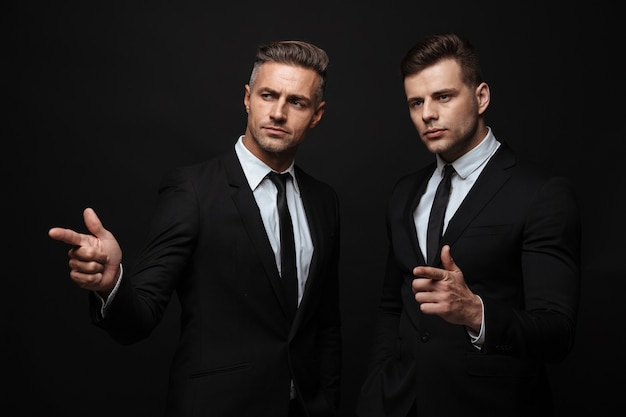 Portrait of serious handsome two businessmen dressed in formal suit pointing fingers and looking aside isolated over black wall