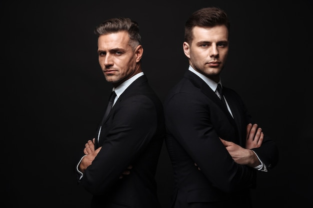 Portrait of serious handsome two businessmen dressed in formal suit posing at camera back to back isolated over black wall