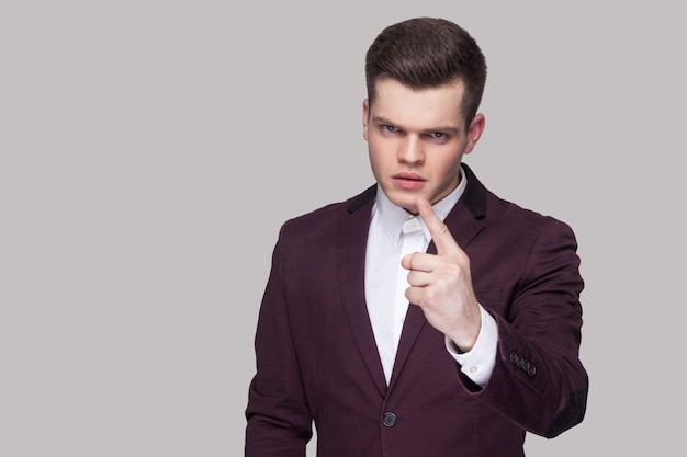 Portrait of serious handsome young businessman in violet suit and white shirt, standing, looking at camera with warning sign and bossy caution. indoor studio shot, isolated on grey background.