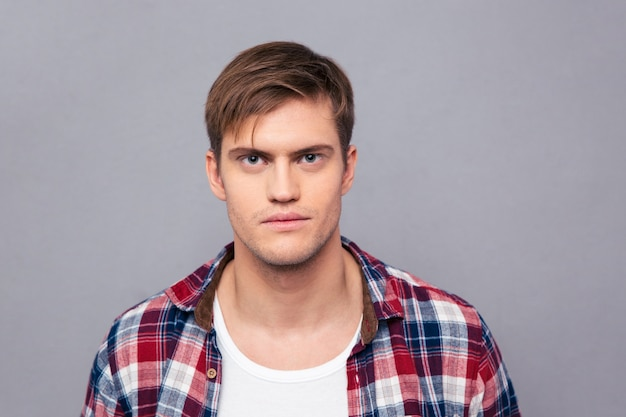 Portrait of serious handsome young man in checkered shirt  over grey wall