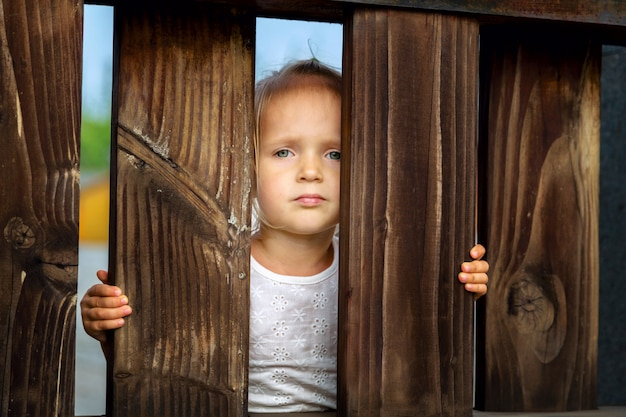 Portrait of serious little girl with blonde hair on a wooden fence