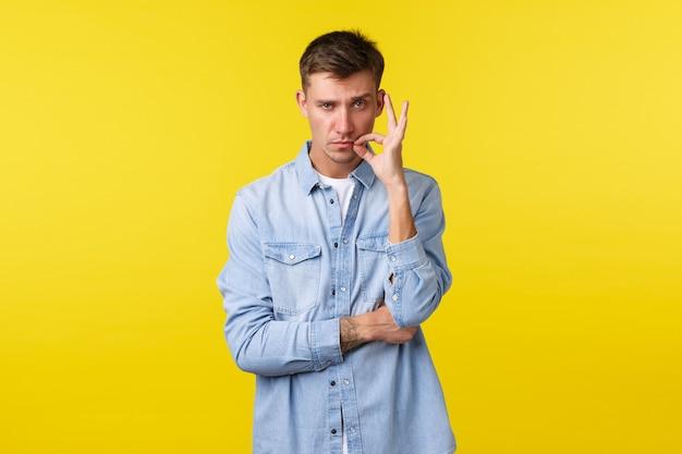Ritratto di un uomo caucasico biondo dall'aspetto serio che chiude la chiusura della bocca sulla serratura, giura di mantenere il segreto e resta in silenzio, sigilla le labbra con la promessa, in piedi determinato su sfondo giallo