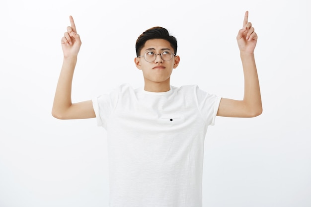 Portrait of serious-looking charming young chinese male student in white t-shirt raising hands