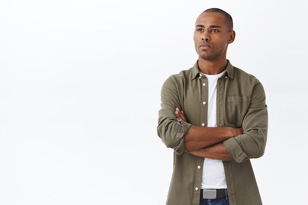Ritratto di giovane afroamericano determinato dall'aspetto serio, che guarda con un'espressione riflessiva focalizzata nello spazio della copia sul lato sinistro