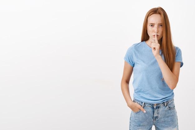 Ritratto di donna dai capelli rossi intensa e prepotente dall'aspetto serio con le lentiggini accigliate che zittiscono con il dito indice sulle labbra chiedendo di non dire a nessuno un segreto importante