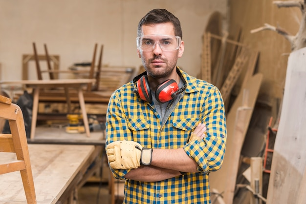 Portrait of a serious male carpenter standing in the workshop Free Photo