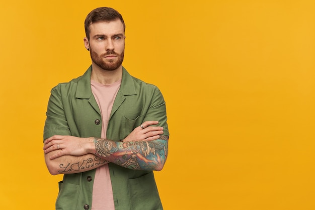 Portrait of serious male with brunette hair and beard. wearing green short sleeves jacket. has tattoo. holds arms crossed. watching to the right at copy space, isolated over yellow wall