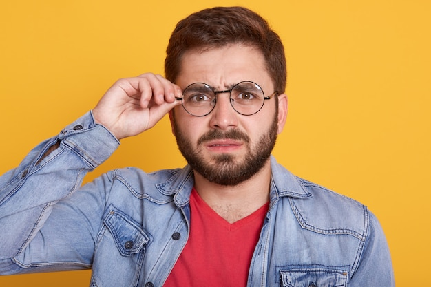 Portrait of serious male with dark hair and beard touching his glasses, male wearing stylish denim jacket, posing against yellow wall