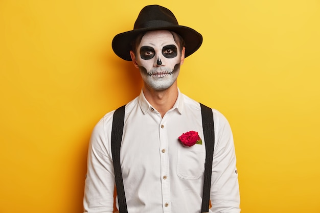 Portrait of serious male zombie wears skull mask, horrible makeup, celebrates mexican holiday, wears black hat and white shirt with suspenders, has red rose in pocket, isolated over yellow background.