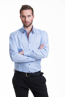 Portrait of serious man in blue shirt and black pants with crossed arms - isolated on white.