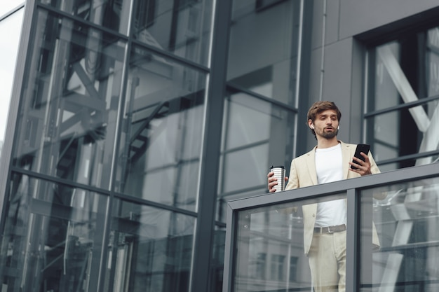Portrait of serious man dressed in trendy business suit having video call on smartphone while standing outdoors with cup of coffee
