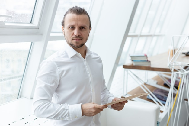 Portrait a serious man  holding a document in his hands standing in the modern interior