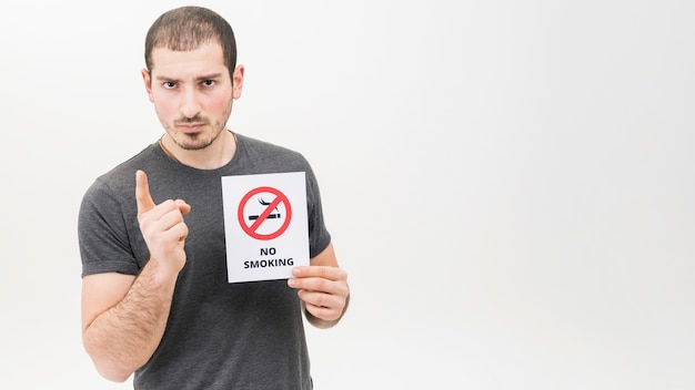 Portrait of a serious man holding no smoking sign pointing finger toward camera