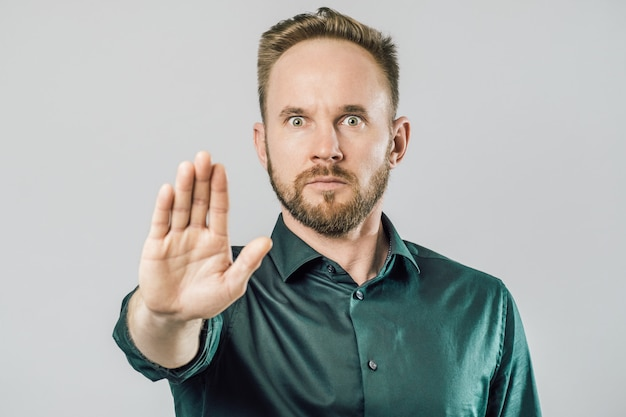 Portrait of a serious man showing stop gesture