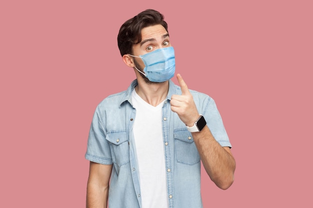 Portrait of serious man with surgical medical mask in blue casual style shirt standing with warming sign and looking at camera to give attention. indoor studio shot, isolated on pink background.