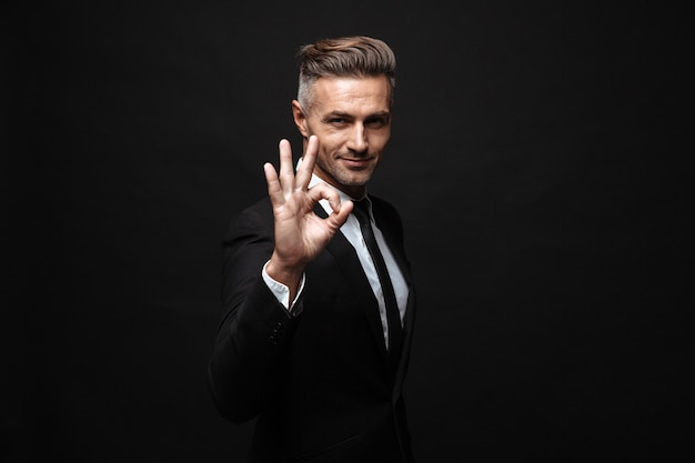 Portrait of serious manly businessman dressed in formal suit gesturing ok sing and looking at camera isolated over black wall