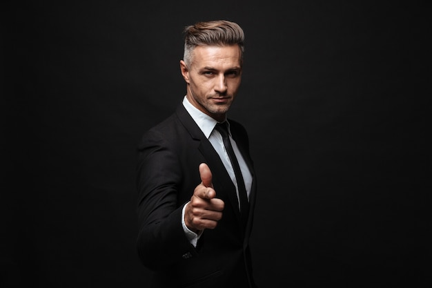 Portrait of serious manly businessman dressed in formal suit pointing finger and looking at camera isolated over black wall