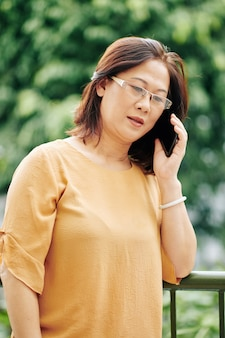 Portrait of serious mature vietnamese woman in glases standing on balcony and talking on phone