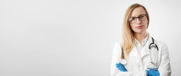 Portrait of serious medical woman with folded arms in latex gloves looking camera, isolated on white