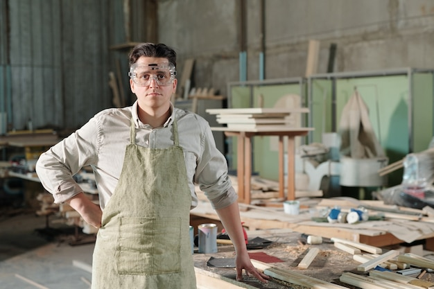 Portrait of serious middle-aged joiner in safety goggles and apron standing at dirty desk with tools and wooden planks in workshop