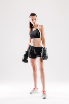 Portrait of a serious motivated woman in boxing gloves standing