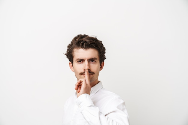 Portrait of serious mustached man wearing shirt holding finger at his lips isolated on white