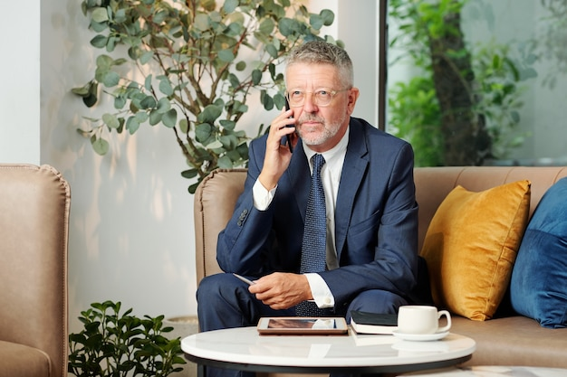 Portrait of serious pensive mature entrepreneur in glasses talking on phone with customer or business partner