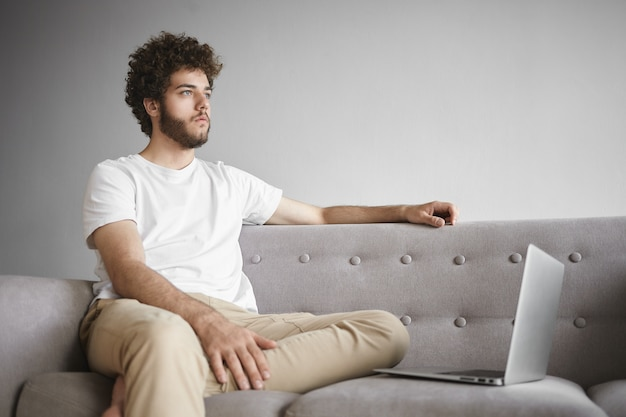 Portrait of serious pensive young caucasian writer having thoughtful look while working on article for online magazine, using wifi on electronic device, sitting in living room on comfortable couch