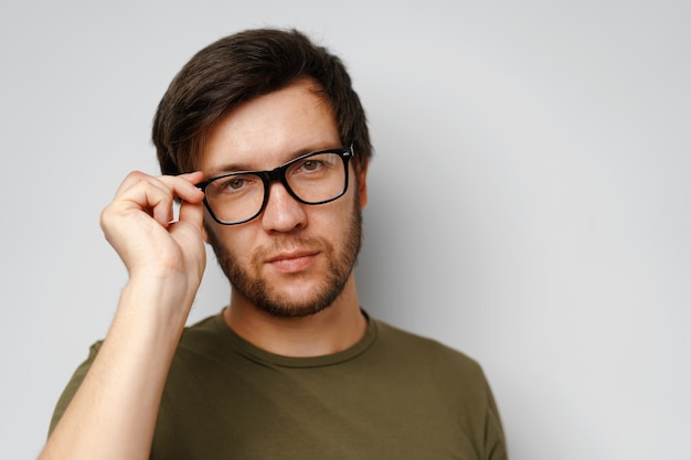 Portrait of a serious pensive young man against grey background close up