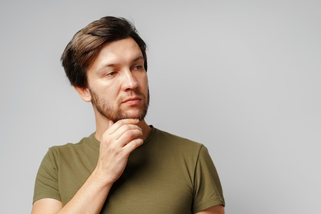 Portrait of a serious pensive young man against grey surface close up
