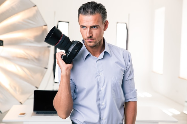 Portrait of a serious photographer holding camera in studip