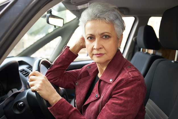 Portrait of serious retired woman with short haircut sitting inside car, passing driving test, feeling nervous.