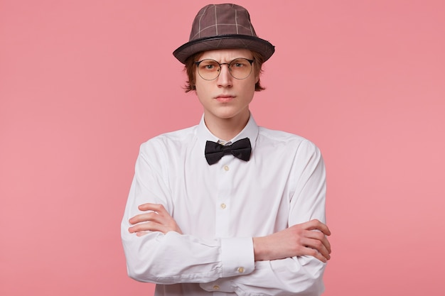 Portrait of serious rude frowning guy in white shirt, hat and black bowtie wears glasses looks angry, standing with arms crossed, isolated on pink background