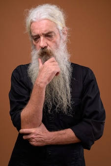 Portrait of serious senior bearded man thinking
