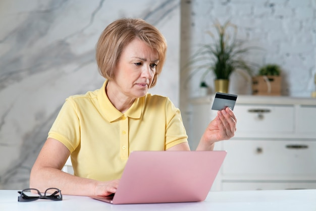 Portrait of serious senior beautiful lady adult mature woman looking at her credit bank card and