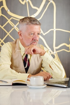 Portrait of serious senior businessman taking off glasses when reading article on laptop screen