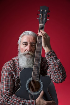 Portrait of a serious senior man with guitar in his hand against red background