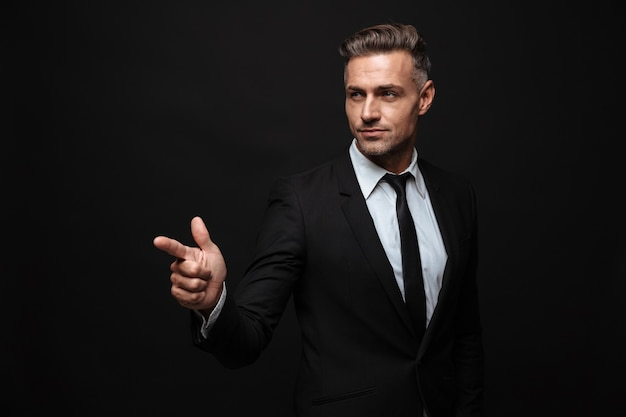 Portrait of serious smart businessman dressed in formal suit pointing finger and looking aside over black wall