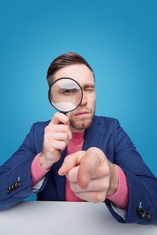 Portrait of serious smart young man pointing at front and looking through magnifying glass while investigating you