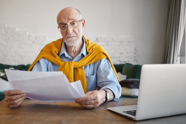 Portrait of serious successful elderly male entrepreneur wearing stylish outfit and accessories checking financial papers in his hands, while working in modern office, using electronic device